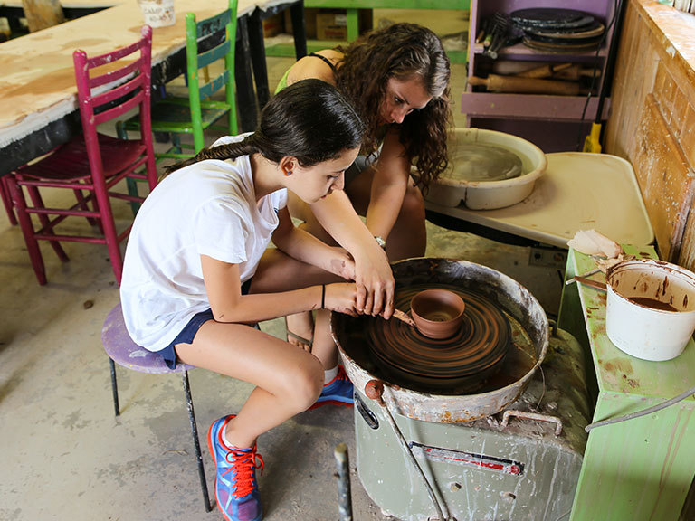 Camper learning pottery