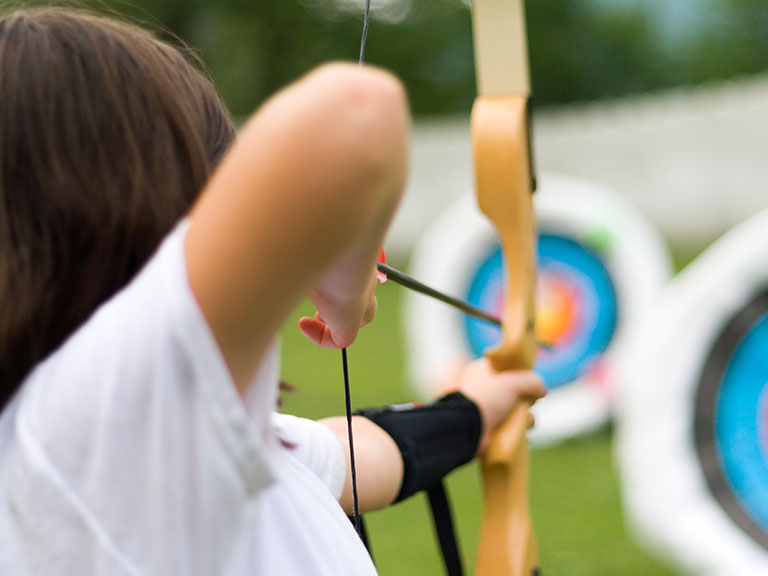 Camper shooting bow and arrow